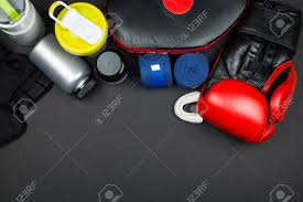 pairs of red leather boxing gloves and blue hand wraps sport supplements on black surface