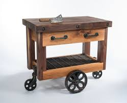 rustic brown wooden kitchen cart with drawers and shelf completed by black metal wheels