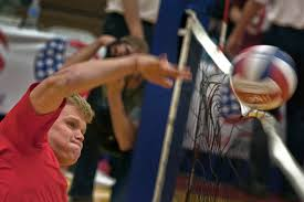 public image man spiking a volleyball over the net  volleyball image 2100x1400