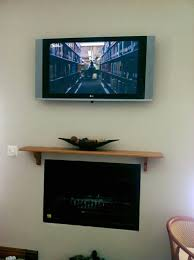 tv wall mounted above fireplace