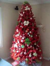 Red artificial Christmas trees - pretty with green holly leaves added as  decorations