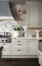 kitchen moldings: glass tile backsplash gorgeous kitchen with ivory shaker kitchen cabinets cabinet moldings marble countertops and cooktop backsplash