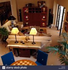 sofa console table. Birdseye View Of Lighted Lamps On Console Table Behind Beige Sofa In Modern Apartment Living Room
