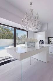 a minimalist white kitchen is spruced up with a modern crystal covered chandelier