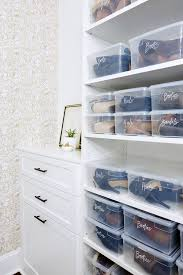 stacked plastic labeled shoe and boot boxes sit on shelves fixed beside a white built in dresser donning bronze pulls accenting jewelry drawers and