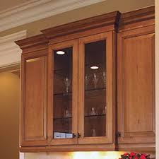 maple cabinets with gl doors display wine gles and have interior lighting and crown molding