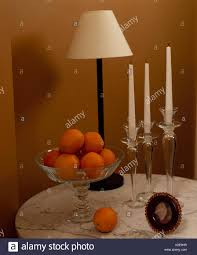 Lamp And Glass Candlesticks With Glass Bol Or Oranges On Round Table