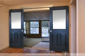 black rolling barn door style doors with large single pane of glass on top