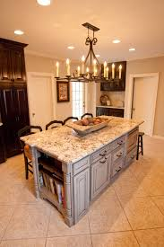 rustic chandelier over white marble top kitchen island with seating and drawer as storage also sweet white ceramic floors in contemporary kitchen ideas