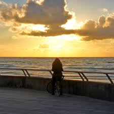 a lonely with a bicycle watching at the sunset over the sea the port in tel aviv jaffa