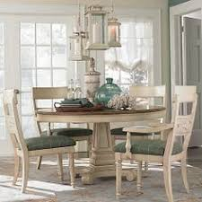 casual dining room lighting. open plan dining room located beside a large kitchen features round salvaged wood table surrounded by gray bamboo chairs with whiteu2026 casual lighting o