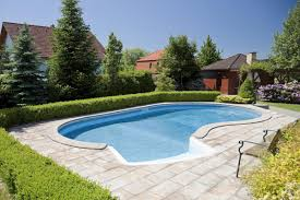 backyard oval fiberglass belowground pool in garden