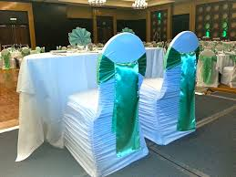 white chairs with sage satin sashes
