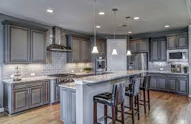 traditional kitchen with gray cabinets and subway tile backsplash with white granite countertop and breakfast bar