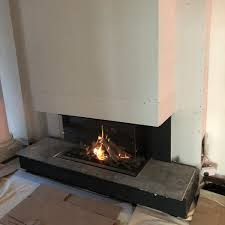 a recent installation in pollockshields glasgow of a dru mestro 105 3 sided log effect fire honed nero granite feature hearth with side panels and chimney