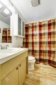 Badezimmer Mit Holzboden Weiße Wand Und Bunter Vorhang Lizenzfreie