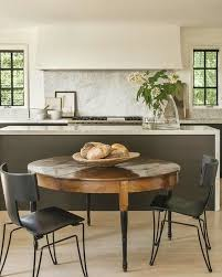 a vintage round dining table with black legs and black modern industrial chairs to create a