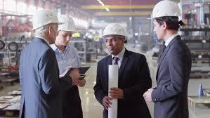 Industrial Engineers Having Meeting At Factory By Pressmaster