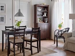 A dining room with a black-brown dining table and chairs with beige seat  covers