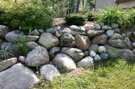 boulders and fieldstone are a great way to create a retaining wall that looks natural and is extremely durable it s not too hard on the budget either