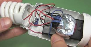 joule thief circuit powering a compact fluorescent lightbulb inside the joule thief and cfl all parts connected and exposed