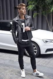 black jeans a sporty print tee a black moto jacket and white chucks