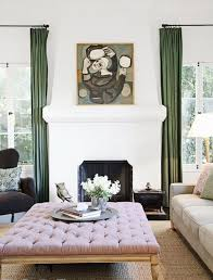 a refined living room with a pink upholstered ottoman that doubles as a coffee table