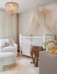 white fur rug wallpaper. chic transitional nursery beige wallpaper decoratively white armchair and beaded chandelier with patterned wallpaper, san diego paired baby room. fur rug
