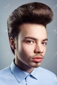 レトロな古典的なポンパドール髪型を持つ若者の肖像画スタジオ撮影し