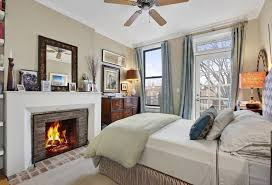 A Smaller Master Bedroom With A Brick Fireplace And A Door Leading Out Onto  A Deck