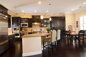 limestone countertops dark kitchen cabinets with light countertops lighting flooring sink faucet island backsplash shaped tile travertine birch wood orange
