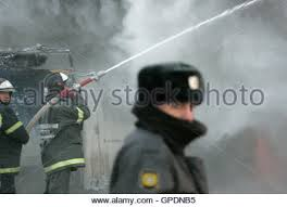 a fire broke out in a household electrical fuse box flames a policeman stands guard while firefighters work at the site of a burnt fair that was