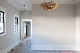 living room light gray walls grey gold chandelier black window sashes whitewashed hardwood flooring light blue doors 5 of 6