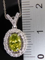 white gold pendant set with an exclusive intense fancy olive yellow green faceted oval shaped diamond and 21 diamonds 1 00 ct in total