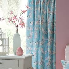 light blue bohemian curtains mixed with white flower vase and pink accessory over white wooden