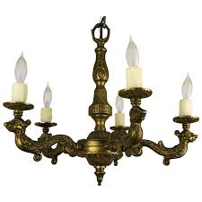1920 s continental 5 arm cast brass chandelier with figural detailed arms
