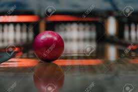 Light Bowling Close Up Shot Of Red Bowling Ball Lying On Alley Under Warm Light