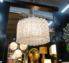 white shaped capiz shell chandelier with table lamp and large wall mirror plus wood table also