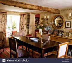 Upholstered Chairs At Antique Oak Table In Cottage Dining Room