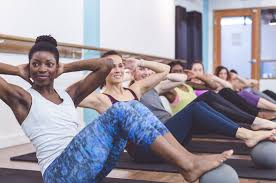 women in yoga cl sitting up with arms