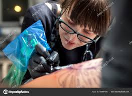 молодая девушка тату мастер на работе стоковое фото Shishkin137