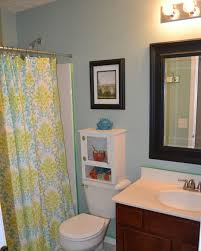 bathroom yellow blue fabric shower curtains added by black wooden picture frames on blue wall