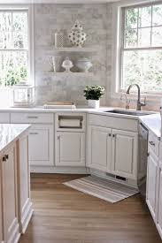white cabinets subway tiles with a carrara marble print white quartz countertops