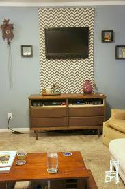 hide TV cables with a fabric panel behind a wall-mounted TV (thefrontpoarch)