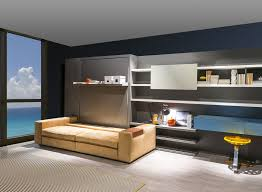 silver tone integrated murphy bed with long bookcase combined light brown couch without backrest on whote hardwood floor as well