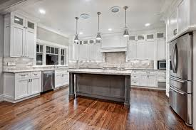 contemporary maple kitchen cabinets in white with white laminate countertop and black knobs also black pulls