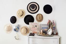Hats in various sizes and shapes hanging above a door