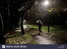 Looking For The Light Through The Pouring Rain A Man Runs Through A Park At Night In The Pouring Rain Stock