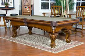 varnished brown wooden pool dining table with gray counter top plus four legs with carving ornaments