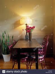 Esszimmer Mit Rosa Stühle Um Holz Tisch Mit Lampe Stockfoto